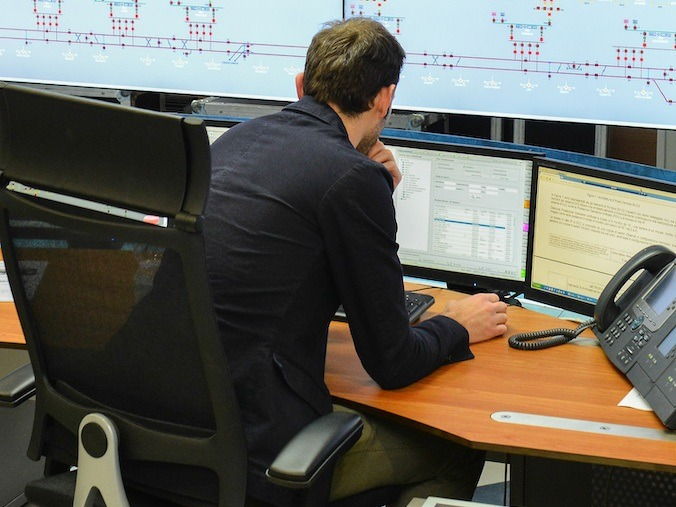 Pipeline controller in control room focusing on pipeline safety management systems (pipeline SMS)