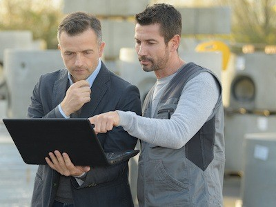 Engineer in the oil field reading report on laptop for Pipeline SMS